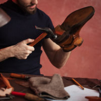 close-up cropped photo of shoemaker repairing shoes by nailing a